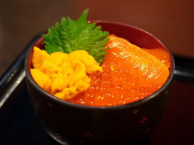 Ciotola di riso giapponese condita con salmone fresco, uova di salmone e ricci di mare (salmone sashimi e uova, uni), pesce crudo commestibile