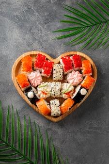 Rotoli giapponesi in piatto a forma di cuore su sfondo grigio cemento vista dall'alto foto verticale vertical