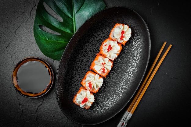 Panini giapponesi con caviale e formaggio filadelfia su un piatto nero vista dall'alto