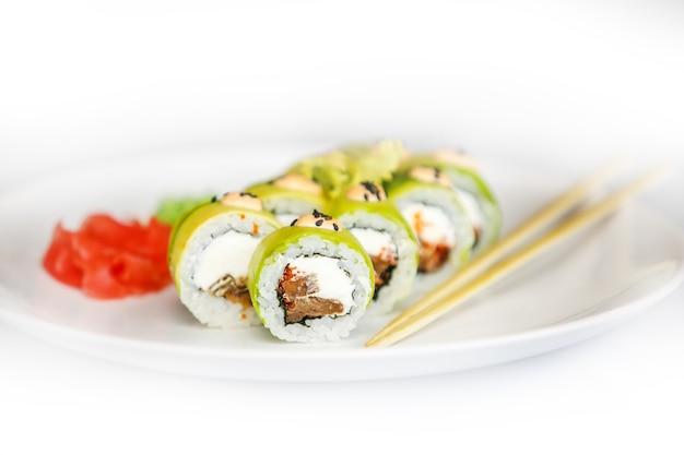 Sushi giapponese di frutti di mare, rotolo e bacchette su un piatto bianco con zenzero e wasabi