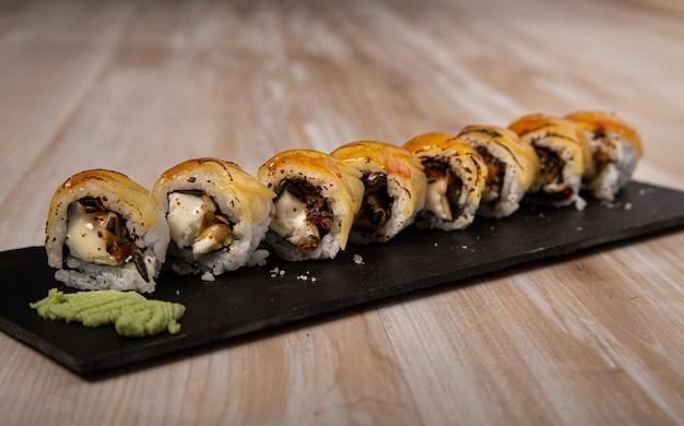 Bordo di sushi giapponese, formaggio di capra urimaki e mela su fondo di legno.