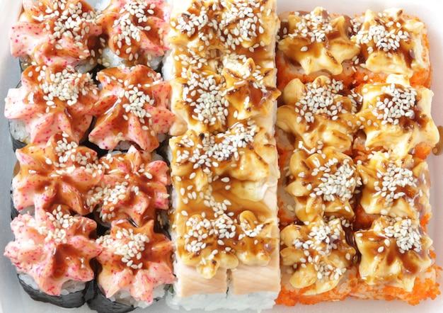 Cibo per sushi giapponese involtini caldi al forno con tonno, salmone, gamberi, granchio e avocado vista dall'alto del sushi