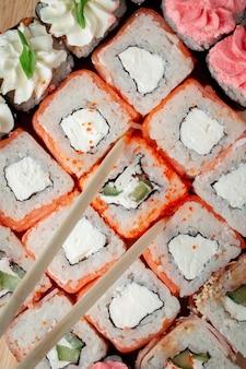 Cibo sushi giapponese. maki e involtini con tonno, salmone, gamberetti, granchi e avocado. vista dall'alto di un assortimento di sushi.