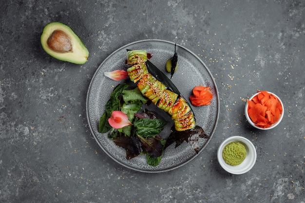 Sushi giapponese - drago verde. avocado, cipolla, salmone e formaggio sushi. vista dall'alto