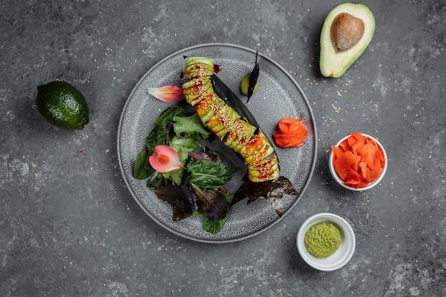 Sushi giapponese - drago verde. avocado, cipolla, salmone e formaggio sushi. vista dall'alto.