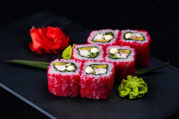 Sushi giapponese in caviale di tobiko uova di pesce volante rosso isolato su oscurità