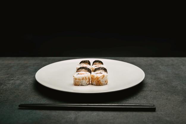 Rotolo di riso giapponese sushi salmone e formaggio presentato in cima al piatto bianco