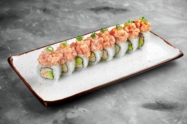 Rotolo di sushi giapponese con granchio, avocado e salmone piccante in un piatto bianco su un tavolo grigio