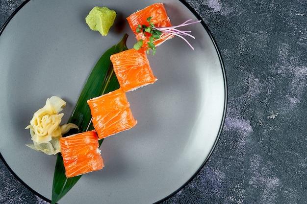 Rotolo di sushi giapponese con salmone e crema di formaggio. roll philadelphia in un piatto grigio su sfondo nero. vista dall'alto
