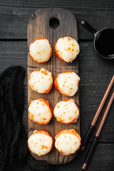 Rotoli di sushi giapponesi denominati ebi al forno con wasabi e set di salmone, sul tavolo di legno nero