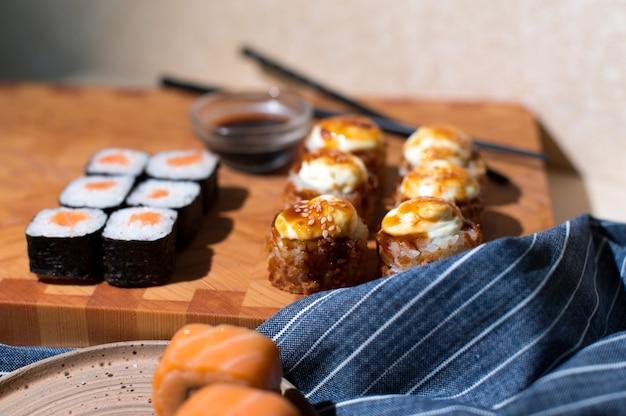 Rotoli di sushi giapponesi serviti su fondo di legno. rotoli di sushi philadelphia, rotolo fritto caldo con panna, maki, bacchette e salsa di soia
