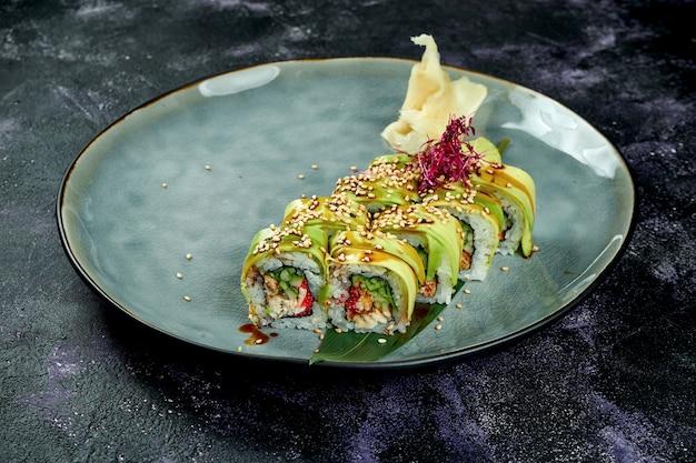 Rotoli di sushi giapponese con anguilla e avocado in un piatto blu su una superficie nera. rotola il drago verde
