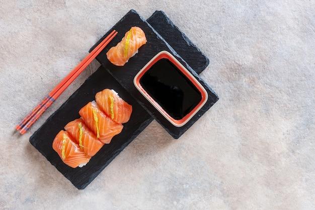Sushi giapponese servito su tagliere di pietra nera. vista dall'alto, primo piano su sfondo scuro.