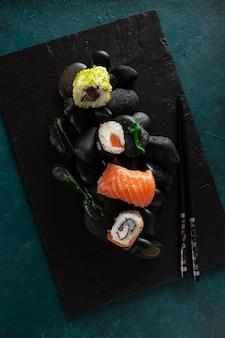 Sushi giapponese servito su pietre nere. vista dall'alto, primo piano su sfondo scuro.