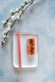 Sushi giapponese servito con rami fioriti di ciliegio primaverile. vista dall'alto, primo piano su sfondo chiaro.