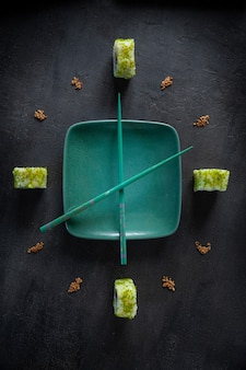Sushi giapponese in servizio foderato a forma di quadrante con lancette. vista dall'alto, primo piano su sfondo scuro.