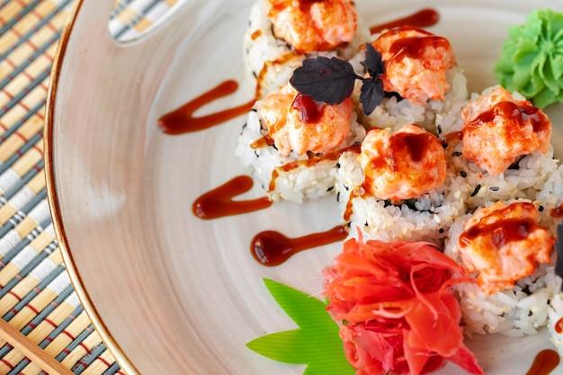Sushi giapponese con semi di sesamo e glassa alla crema su sfondo grigio