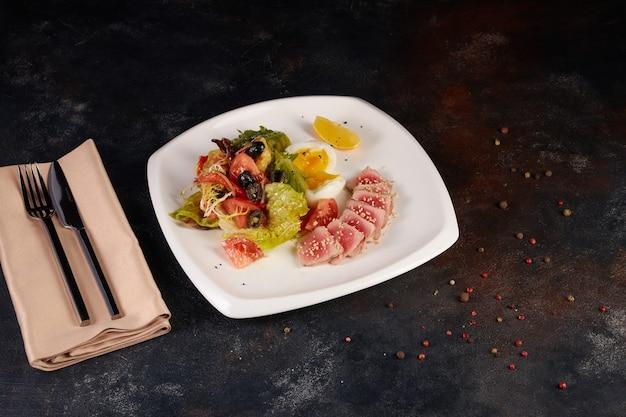 Insalata tradizionale giapponese con pezzi di tonno ahi grigliato medio-raro e sesamo con insalata di verdure fresche su un piatto