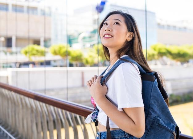 Donna giapponese con uno zaino all'aperto, guardando in alto