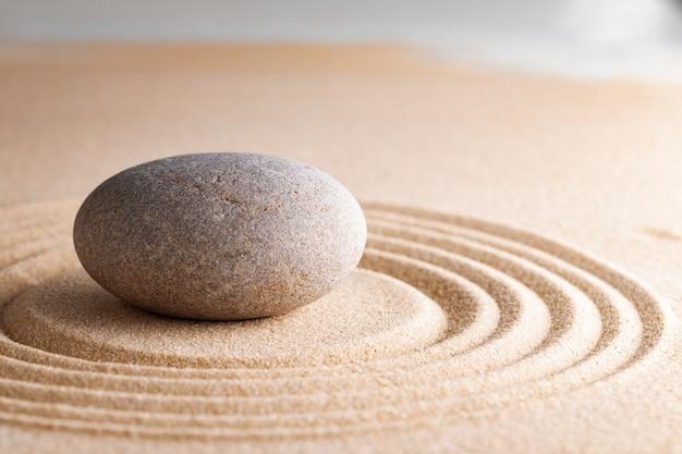 Giardino zen giapponese con pietra nella sabbia rastrellata