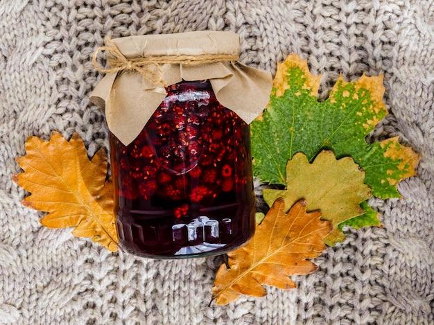 Un barattolo di marmellata di lamponi brillante, un maglione e foglie d'autunno.