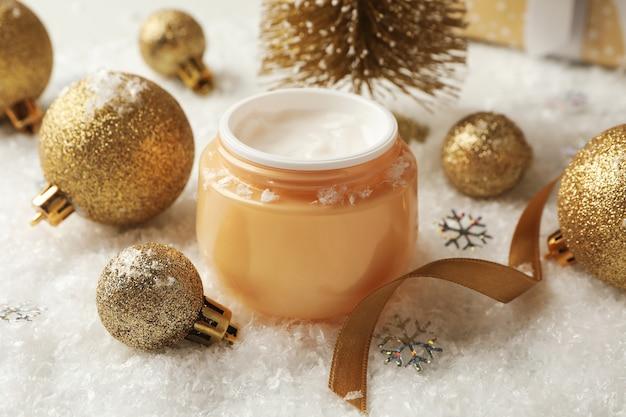 Vasetto di crema cosmetica e accessori natalizi su sfondo con neve decorativa