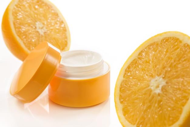 Vaso per crema cosmetica e metà di arance su una parete bianca. cura della pelle. cosmetico naturale.