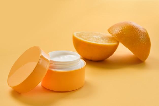 Un vasetto di crema cosmetica e un'arancia tagliata a metà su una parete gialla. cosmetico naturale.