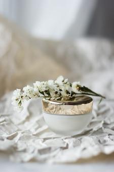 Un barattolo di crema di close-up. crema per il viso con fiori bianchi in barattolo. crema viso in barattolo di vetro con copertura dorata