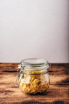 Barattolo pieno di fiocchi di mais su una superficie di legno