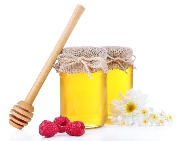 Vaso pieno di delizioso miele fresco e fiori selvatici, isolato su bianco