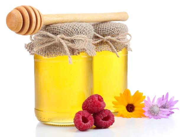 Vaso pieno di delizioso miele fresco e fiori selvatici, su fondo bianco
