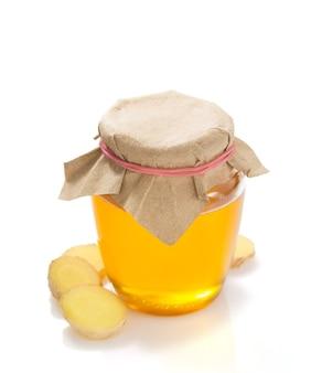 Barattolo di miele e zenzero isolato su bianco