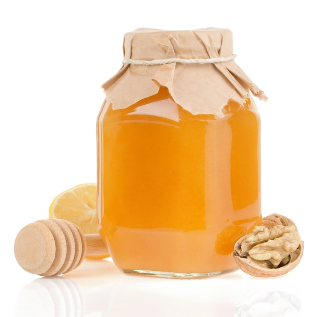 Barattolo di miele e limone isolato su bianco