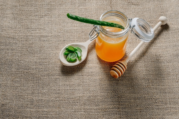Un barattolo di miele e un cucchiaio con una foglia di aloe vera tritata su una tela con copia spazio.