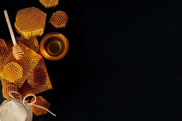 Vasetto di miele con nido d'ape sul tavolo nero, vista dall'alto. spazio per il testo.