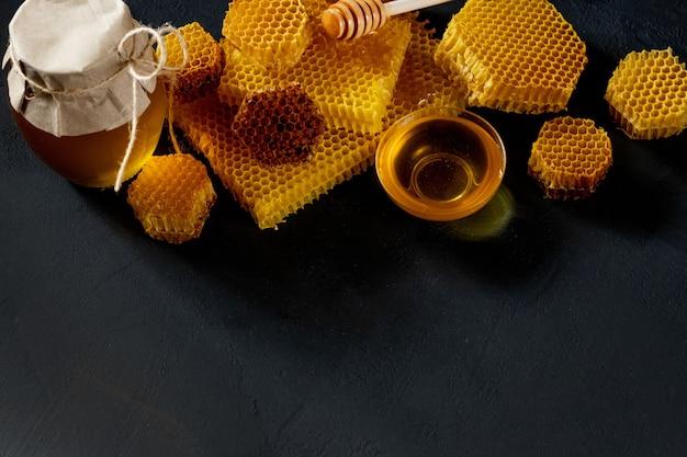Vasetto di miele con favo sulla tavola nera, vista dall'alto. spazio per il testo.