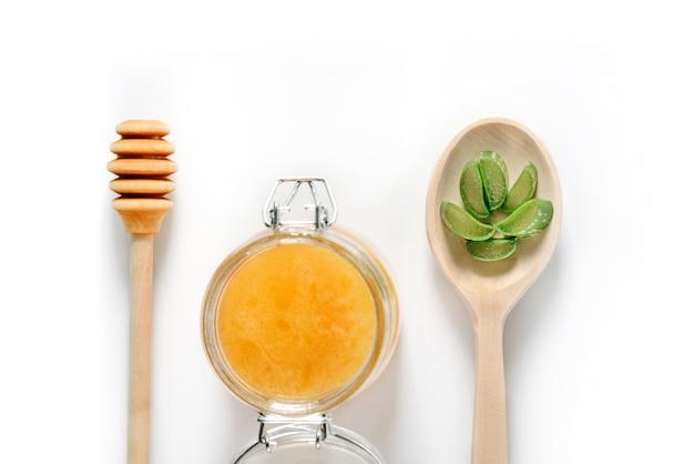 Vasetto di miele, un cucchiaio di legno per miele e un cucchiaio con foglie di aloe vera tritate.