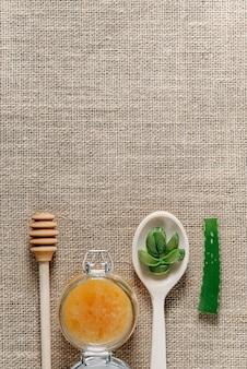 Vasetto di miele, un cucchiaio di legno per il miele e un cucchiaio con foglie di aloe vera tritate