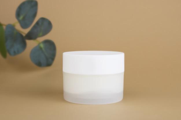 Un vasetto di crema idratante su fondo beige sabbia. mockup di contenitore di plastica bianco