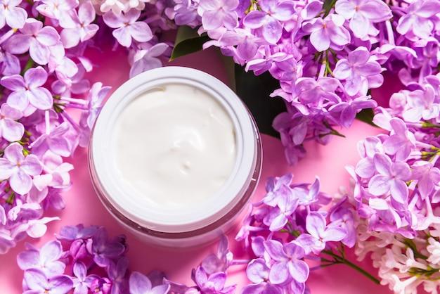 Barattolo di crema per il viso naturale con fiori lilla su sfondo rosa