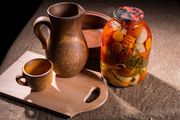 Barattolo di conserve di verdure sott'aceto sulla superficie del tavolo rivestita di tela rustica accanto a oggetti di artigianato in legno intagliato - brocca, tazza, ciotola e tagliere in legno