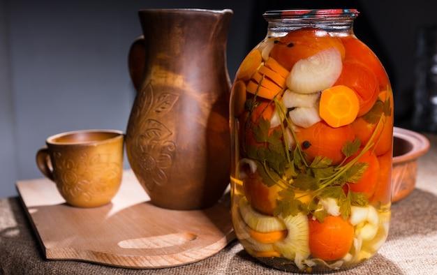 Barattolo di conserve di verdure sottaceto sulla superficie del tavolo accanto a oggetti di artigianato in legno intagliato - brocca, tazza, ciotola e tagliere in legno