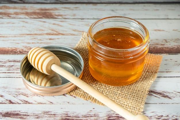 Vasetto di miele puro dalle api con il suo bastoncino di miele in legno sul coperchio del barattolo su un vecchio tavolo rustico.