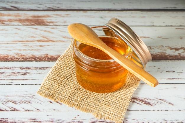 Vasetto di miele puro dalle api con un piccolo cucchiaio di legno su un tavolo rustico.