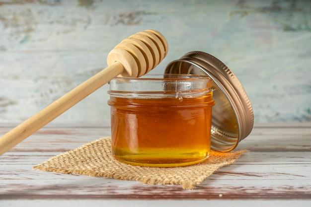 Vasetto di miele puro dalle api con il bastoncino di miele in legno appoggiato sul barattolo su un vecchio tavolo rustico.