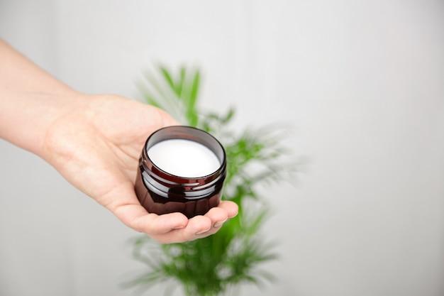 Vasetto di puro burro di karitè in mano femminile cosmetici idratanti naturali prodotto per la cura della pelle e dei capelli