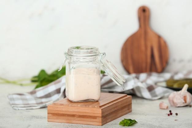 Vasetto di salsa gustosa sul tavolo bianco
