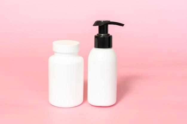 Vaso per vitamine o integratori alimentari e sfondo rosa mockup bottiglia pompa. prodotto di bellezza naturale per la cura della pelle. presentazione del marchio e della confezione.