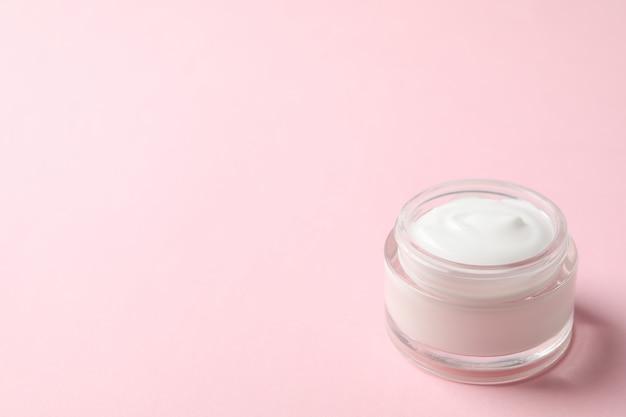 Barattolo di crema invernale per pelle su sfondo rosa, spazio per il testo.